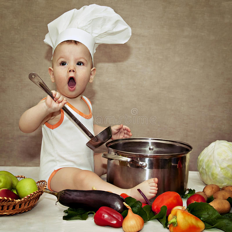Little baby in a chef's hat and ladle in hand royalty free stock photography