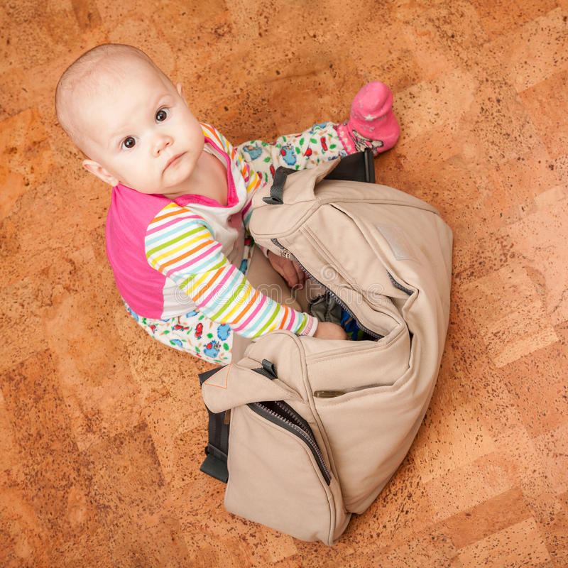 Little baby delves into the bag. Little brown eyed Caucasian baby delves into the bag stock images
