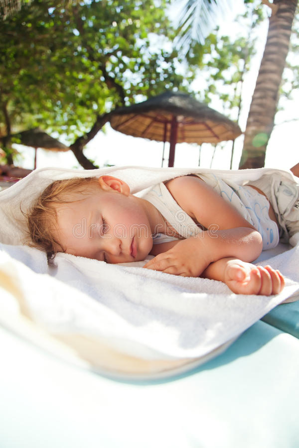Little baby girl asleep on a chaise lounge stock images