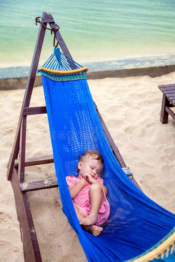 Little baby girl asleep outdoors on a hammock at the sea beach royalty free stock photos
