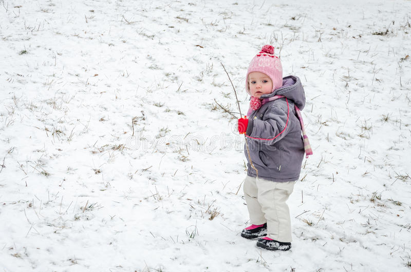 Little baby girl beautiful winter day playing in the snow wearing a jacket hooded down jacket, trousers, hat and gloves stock photography