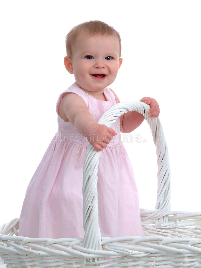 Little Baby Girl in a Big Basket. Smiling baby girl standing in a big wicker basket royalty free stock photography