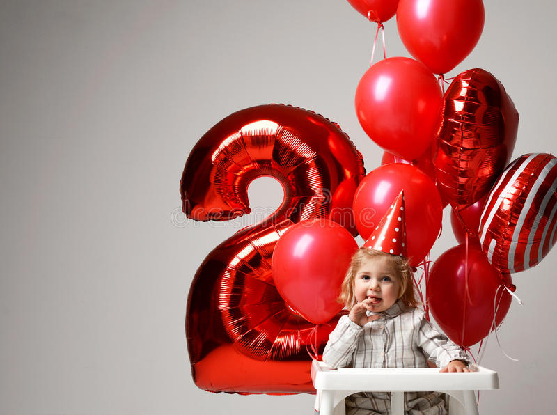 Little baby girl celebrate her second birthday with sweet cake o. N a light party background with red colorful balloons decorations stock photography