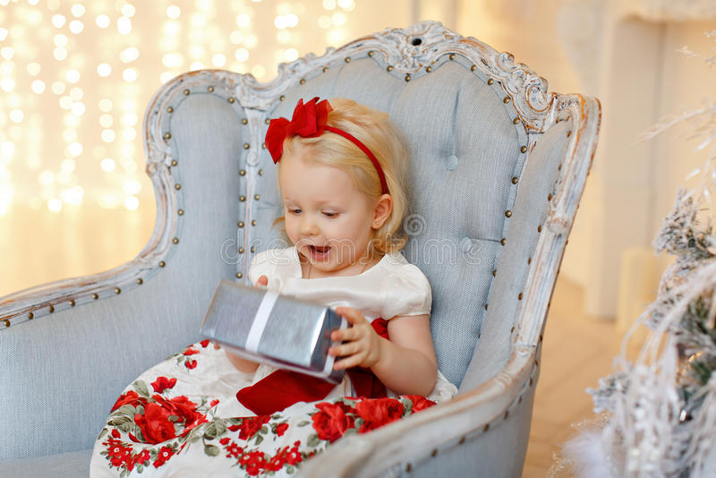 Little baby girl charming blonde in a red dress sitting in a chair against a background of Christmas trees and wonders present, i royalty free stock photo