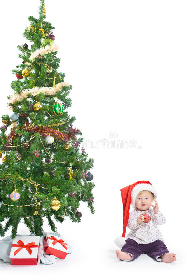 Little baby girl with a Christmas tree and a ball royalty free stock photos
