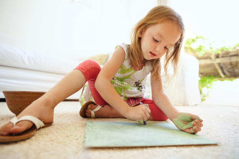 Little baby girl coloring picture at home stock photo