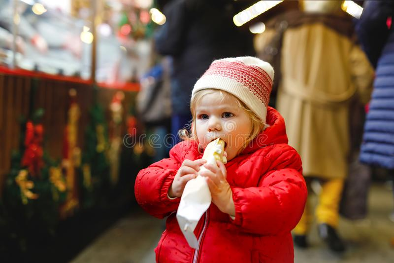 Little baby girl, cute child eating bananas covered with chocolate, marshmellows and colorful sprinkles near sweet stand royalty free stock photography