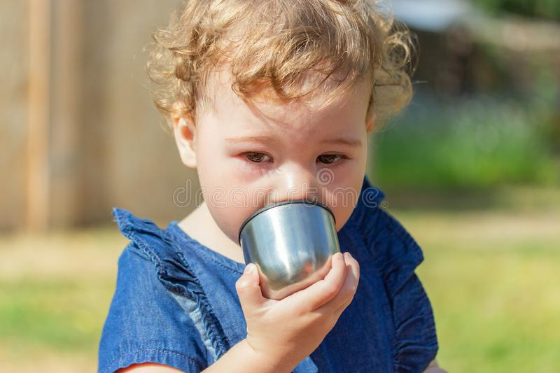 Little baby girl in a denim dress drinks from a metal cup, portrait of 1 year baby close-up. Caucasian girl holds a cup from a royalty free stock images