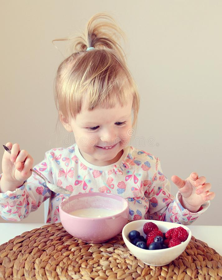 Little baby girl eating healthy breakfast at home, berries and yogurt royalty free stock photo