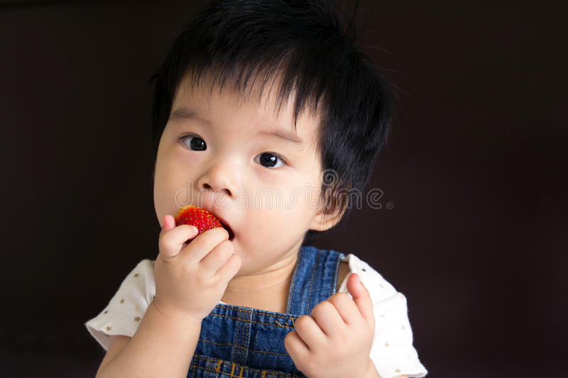 Little baby girl eating strawberry stock photos