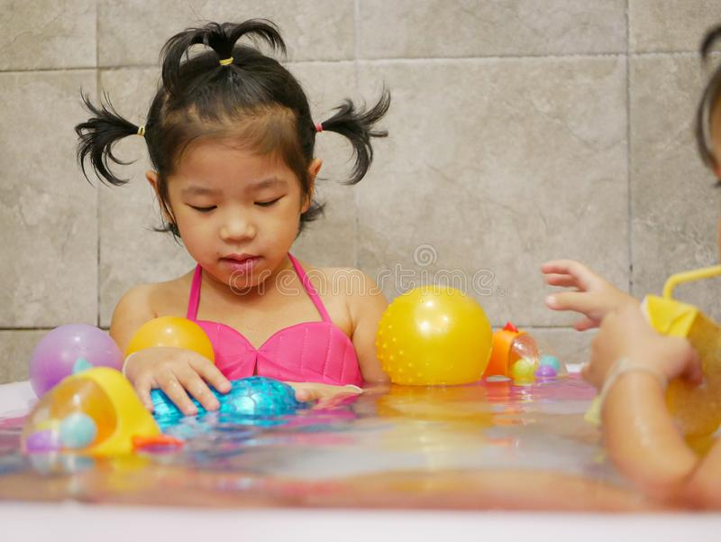 Little baby girl enjoys getting dressed as a mermaid and playing water in a small pool at home. Little Asian baby girl enjoys getting dressed as a mermaid and royalty free stock photos