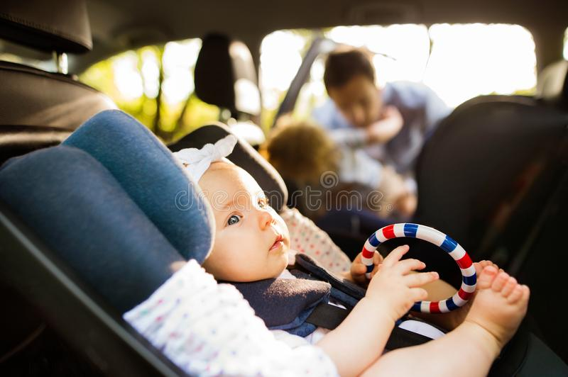 Little baby girl fastened with security belt in safety car seat. stock photography