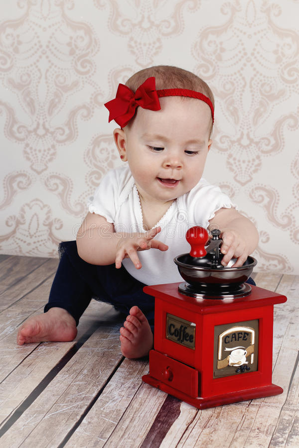 Little baby girl helping in the kitchen stock photo