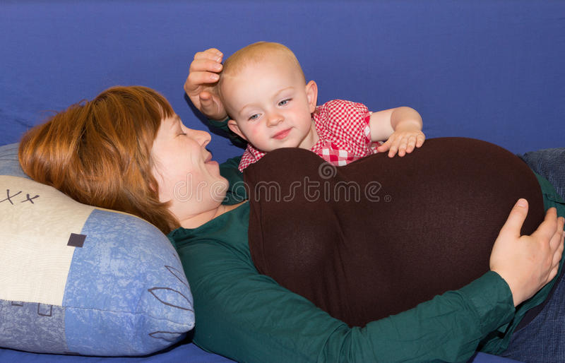 Little baby girl with her pregnant mother stock photos