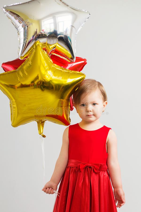 Little baby girl holding balloons in the form of stars. Young gi royalty free stock images