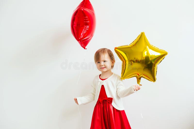 Little baby girl holding balloons in the form of stars. Young gi stock photography