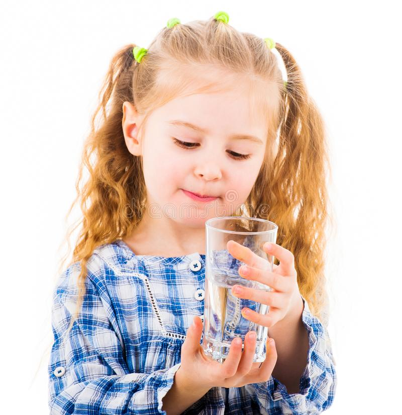 Little baby girl holding a glass of pure water royalty free stock photography