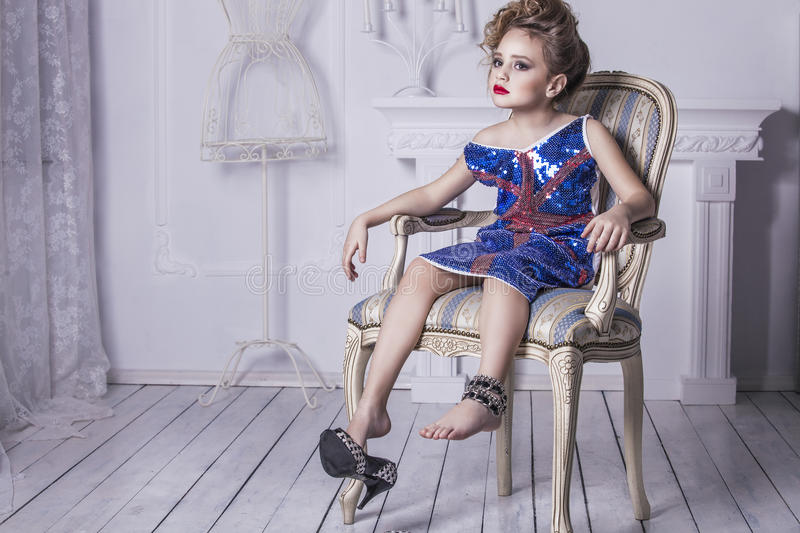Little baby girl in the image of a glamorous model in a luxurious interior. Mimics adult stock photo