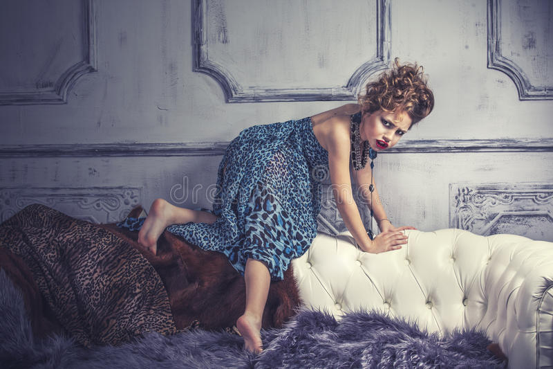 Little baby girl in the image of a glamorous model in a luxurious. Interior mimics adult royalty free stock image