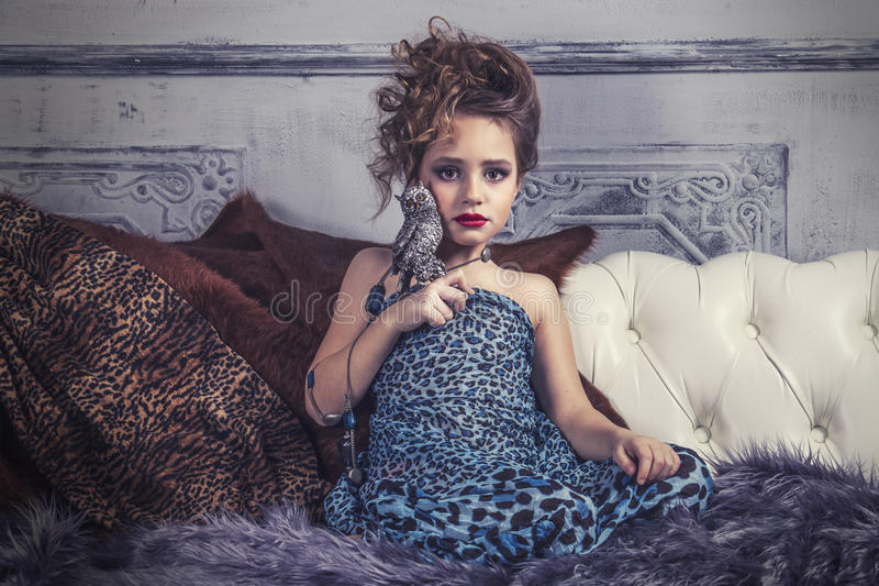 Little baby girl in the image of a glamorous model in a luxurious. Interior mimics adult stock images