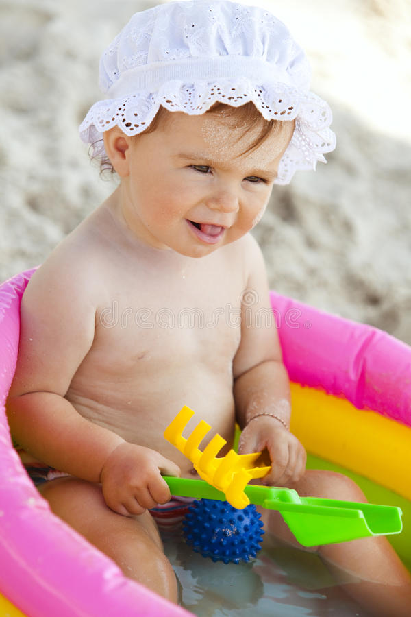 Little baby girl in the inflatable swimming pool royalty free stock images