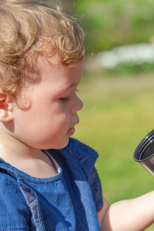 Little baby girl in jeans looks in a cup, portrait of a 1 year baby close-up. Caucasian girl with curly hair holds a cup from a stock images