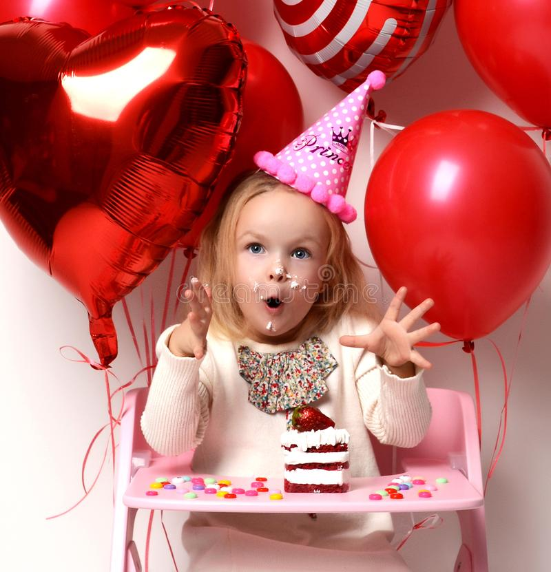 Little baby girl kid celebrate birthday party with sweet cake and candies happy screaming. Background with red colorful balloons decorations stock photography