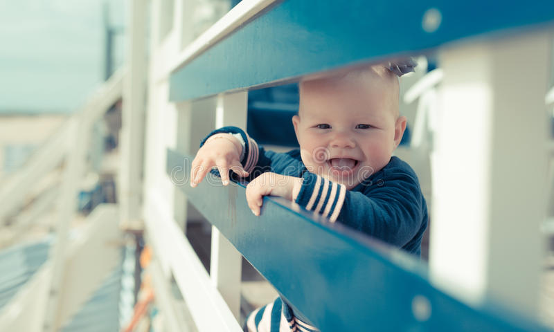 Little baby girl laughing and having fun on a beachhouse. Smiling lovely baby on the beach stock photo