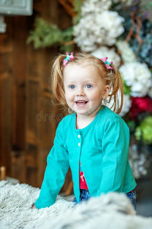 Little baby girl laughs in the room. The concept of childhood an stock photos
