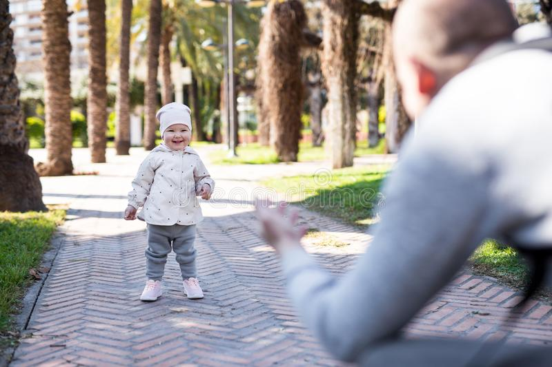 Little baby girl learning to walk in summer park. First steps concept - little baby girl learning to walk with father in summer park stock image