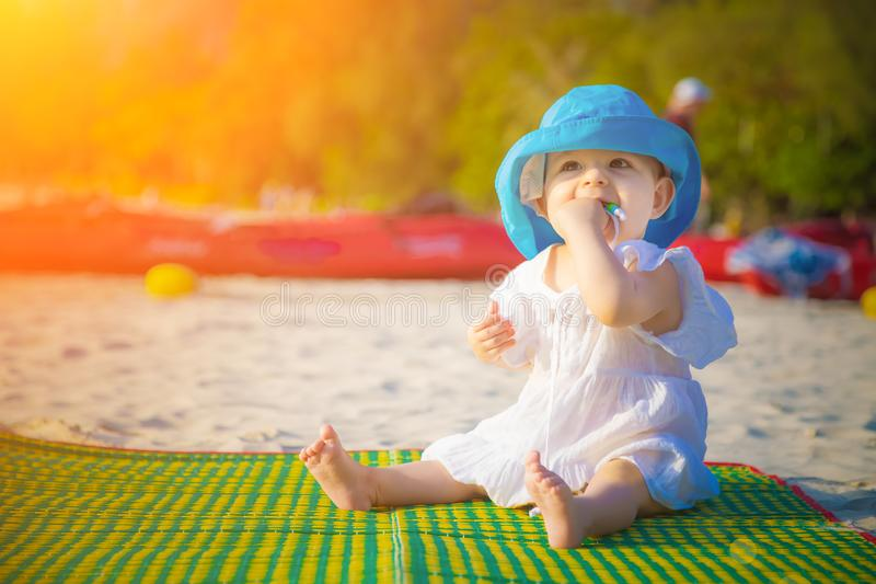 Little baby girl 8 month is sitting on the sandy beach in blue hat and white dress. She is impressed of the sea stock photos