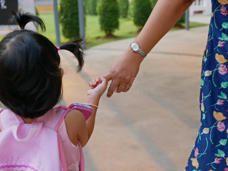 Little baby girl holding her mother`s hand / finger, while walking to the classroom on her first day at school stock photos