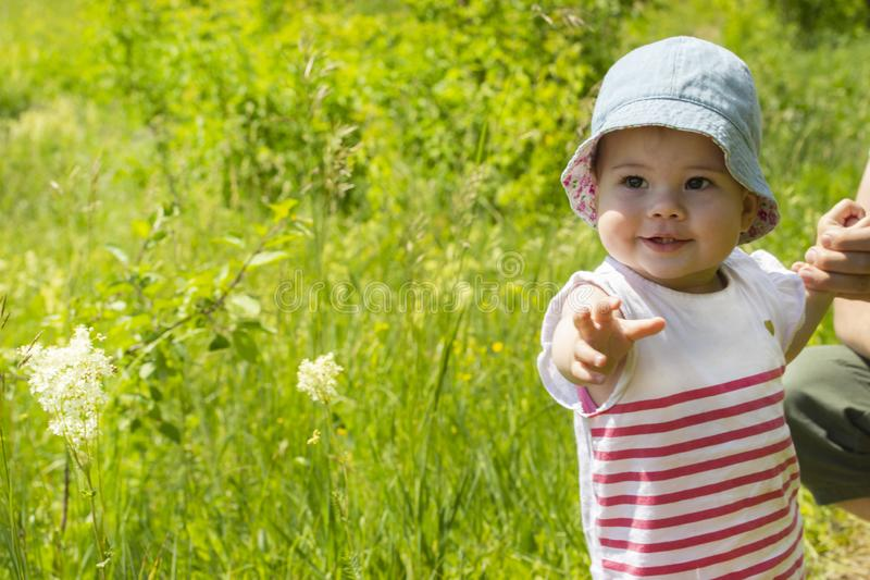 Little baby girl, 9 months old, walks in a meadow with her parents. Portrait of a smiling child in panama and dress. The girl stock photo