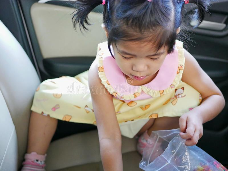 Little baby girl picking up elastic hairbands she dropped on the seat - teaching your children responsibility. Little Asian baby girl picking up elastic royalty free stock photo