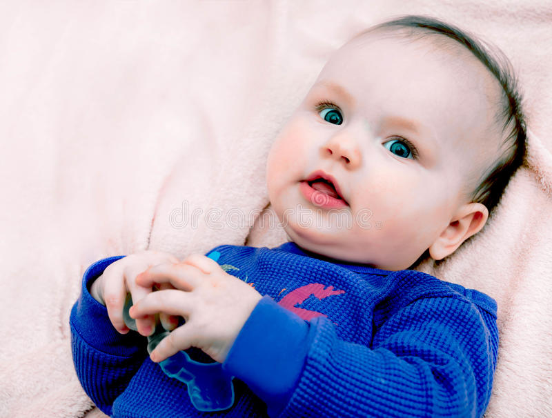 Little baby girl on pink background in purple blouse royalty free stock photos