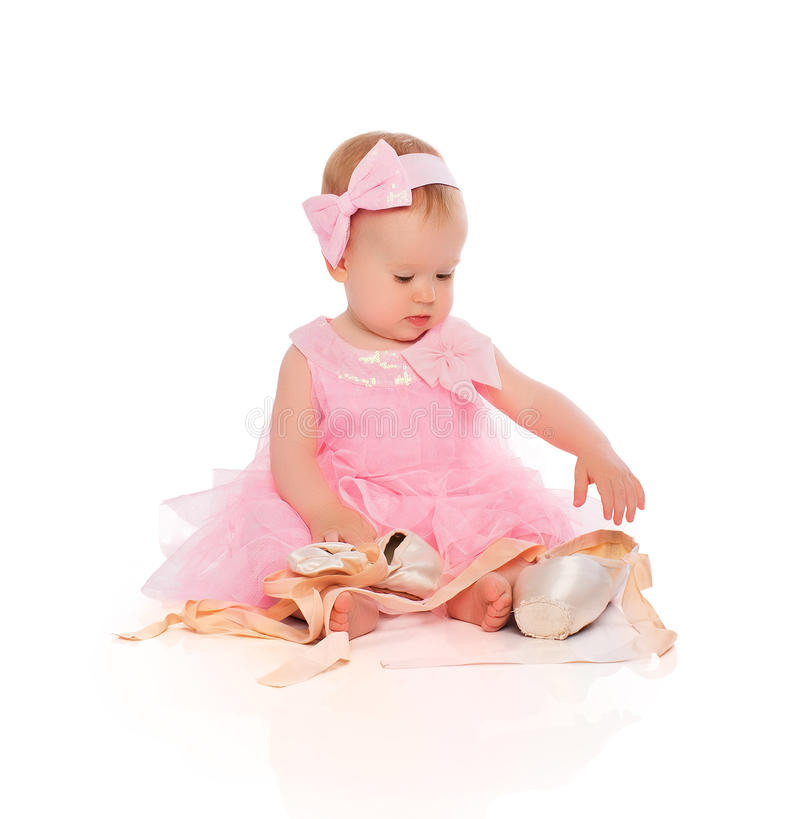 Little baby girl in a pink ballerina dress with pointe shoes stock photography