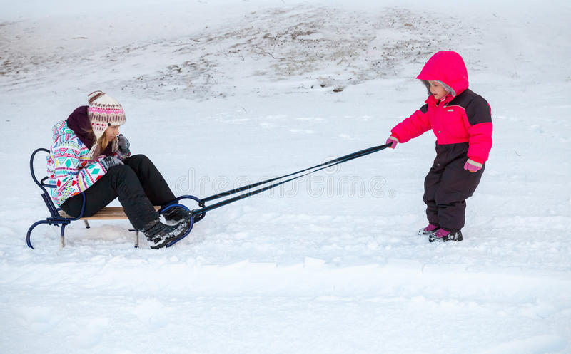 Little baby girl in pink pulling a sled with sister royalty free stock photos