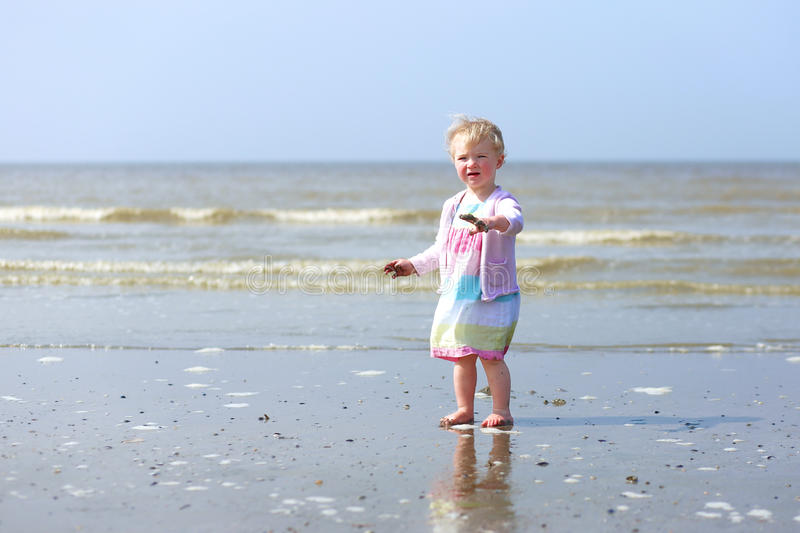 Little baby girl playing on the beach stock images
