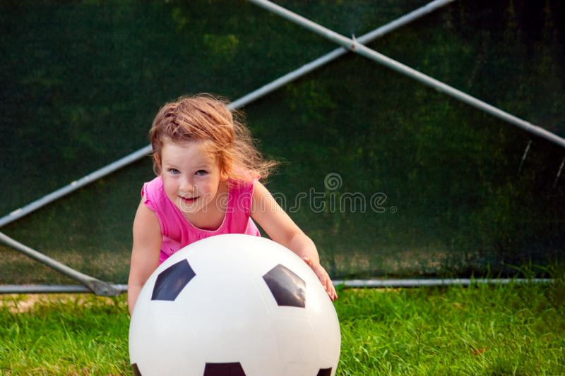 Little baby girl playing with a huge soccer ball. royalty free stock image