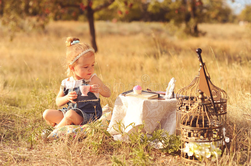 Little baby girl playing outdoors stock photo
