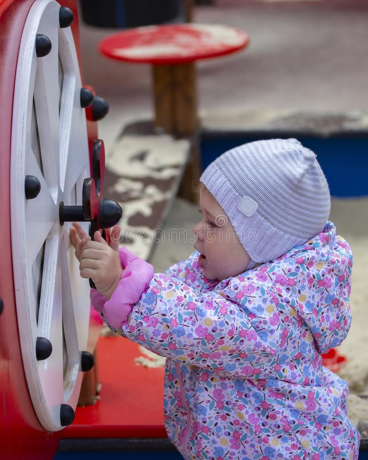 Little baby girl playing on the playground. One-year-old child in a hat and jacket plays with children`s carousels and sports. Equipment. A kid walks in warm stock photos
