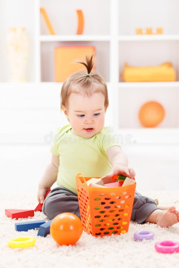Little baby girl playing with toys stock images