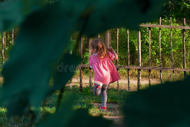 Little baby girl playing in the yard near the house stock photography