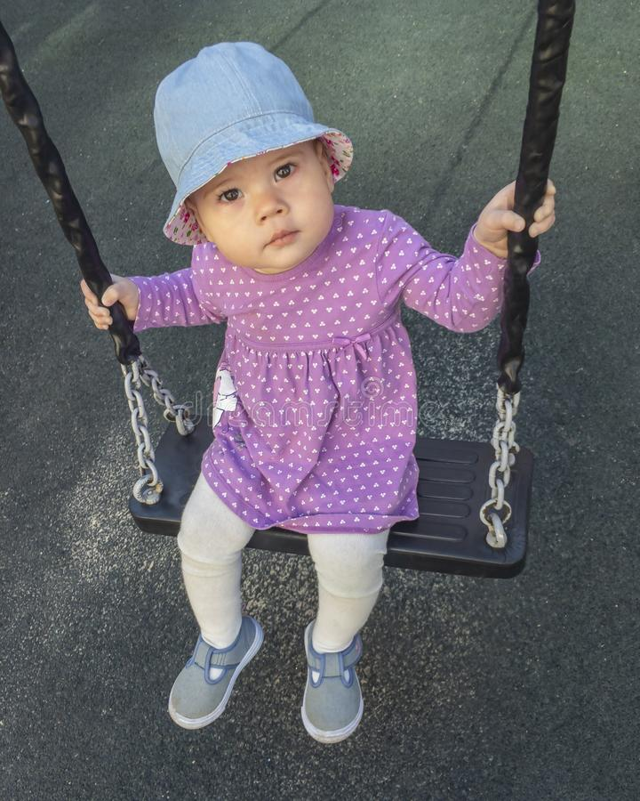 Little baby girl in a purple dress riding on a swing, a dark background, a portrait of a child. Cute serious young girl sitting on. A swing in denim shoes and a royalty free stock images