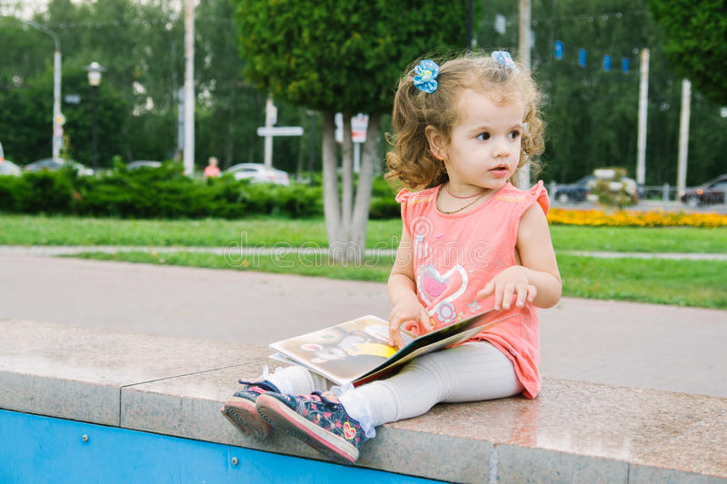 Little baby girl reading her favorite book sitting royalty free stock photo
