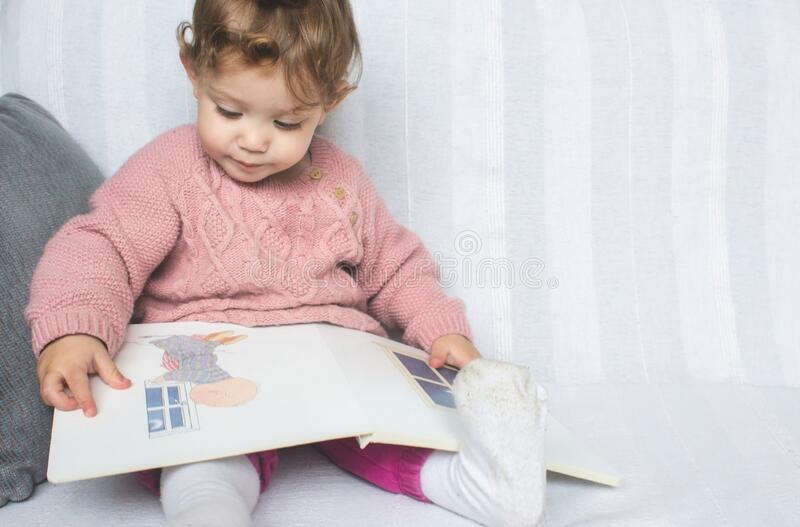 Little baby girl reading a picture book on a white sofa royalty free stock image