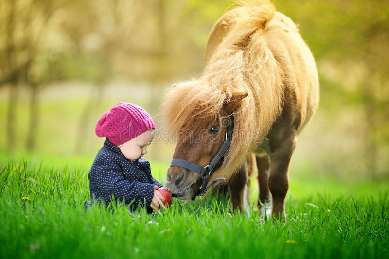 Little baby girl with red apple and pony stock photography