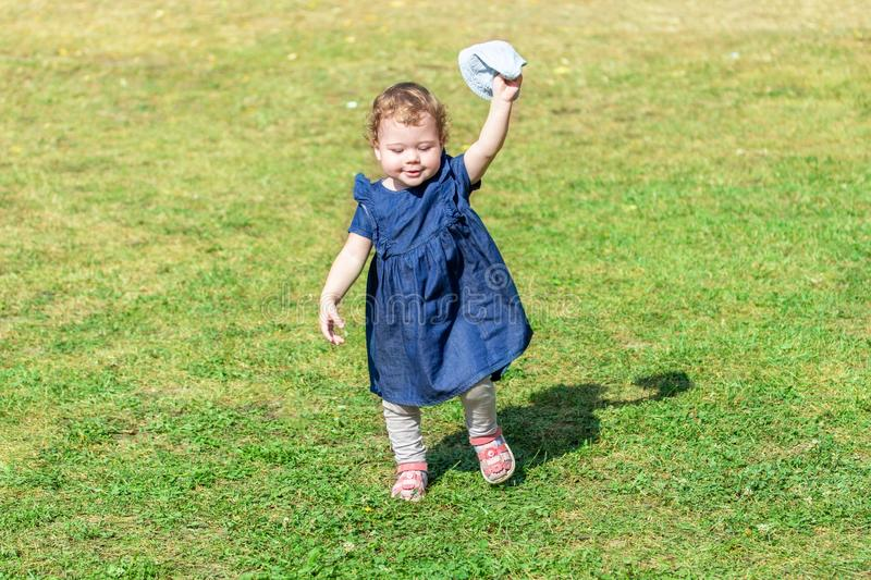 Little baby girl runs across the field in a denim dress with a panama in her hands. cheerful little girl learning to walk royalty free stock photography