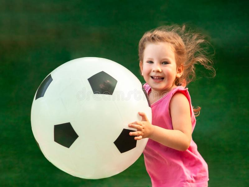 Little baby girl runs with a huge soccer ball. The girl rejoices and smiles. Baby is growing and becoming a little cheerleader of a big European game royalty free stock photos