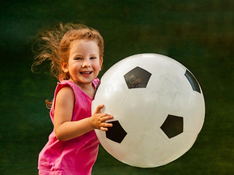 Little baby girl runs with a huge soccer ball. The girl rejoices and smiles. Baby is growing and becoming a little cheerleader of a big European game stock photography